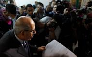Reporters flank Egyptian reform leader and Nobel Peace Prize laureate Mohamed ElBaradei after receiving his ballot sheet while preparing to vote at a polling station in Giza, Egypt Thursday, Dec. 15, 2011. Islamists and liberals made accusations of abuses during the second round of Egypt's first post-Hosni Mubarak parliamentary elections as voters cast ballots Thursday in mostly rural parts of the country. (AP Photo/Nasser Nasser)