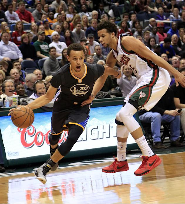 En la imagen, el jugador de los Warriors de Golden State Stephen Curry, a la izquierda, se acerca a canasta defendido por el jugador de los Bucks de Milwaukee Michael Carter-Williams en su partido de