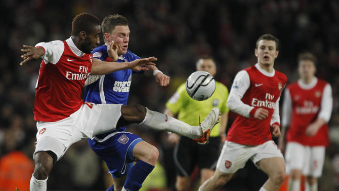 Arsenal's Johan Djourou, left, competes for the ball with Ipswich Town's Connor Wickham during the English League Cup semifinal soccer match between Arsenal and Ipswich Town at the Emirates stadium in London, Tuesday, Jan. 25, 2011.  (AP Photo/Matt Dunham) NO INTERNET/MOBILE USAGE WITHOUT FOOTBALL ASSOCIATION PREMIER LEAGUE(FAPL)LICENCE. CALL +44 (0) 20 7864 9121 or EMAIL info@football-dataco.com <mailto:info@football-dataco.com> FOR DETAILS