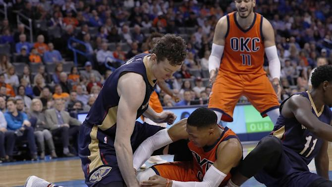 New Orleans Pelicans center Omer Asik, left, and Oklahoma City Thunder guard Russell Westbrook, right, fight for a loose ball during the first half of an NBA basketball game in Oklahoma City, Sunday, Dec. 4, 2016. (AP Photo/Alonzo Adams)