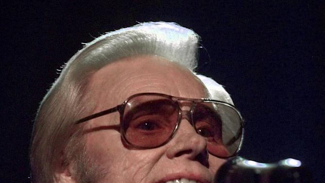 "FILE - In this June 1, 1999 file photo, Country music legend George Jones is shown during a performance in Nashville.  Jones, the peerless, hard-living country singer who recorded dozens of hits about good times and regrets and peaked with the heartbreaking classic ""He Stopped Loving Her Today,"" has died. He was 81. Jones died Friday, April 26, 2013 at Vanderbilt University Medical Center in Nashville after being hospitalized with fever and irregular blood pressure, according to his publicist Kirt Webster. (AP Photo/John Russell, file)"