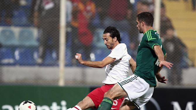 Turkey's Bilal Kisa, left, and Aaron Hughes of Northern Ireland fight for the ball during their friendly soccer match in Adana, Turkey,  Friday, Nov. 15, 2013.(AP Photo)