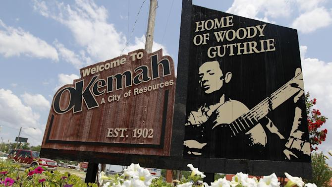 A sign welcomes people to Okemah, Oklahoma, the home of Woody Guthrie, in Okemah, Okla., Friday, July 13, 2012. Okemah is celebrating the Guthrie Centennial with the 15th annual Woody Guthrie Folk Festival. (AP Photo/Sue Ogrocki)
