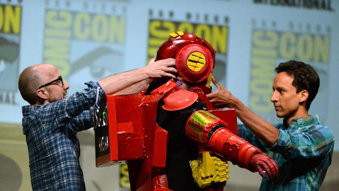 "Dan Harmon, center, is helped out of a costume by Jim Rash, left, and Danny Pudi during the ""Community"" panel on Day 5 of Comic-Con International on Sunday, July 21, 2013, in San Diego. (Photo by Jordan Strauss/Invision/AP)"