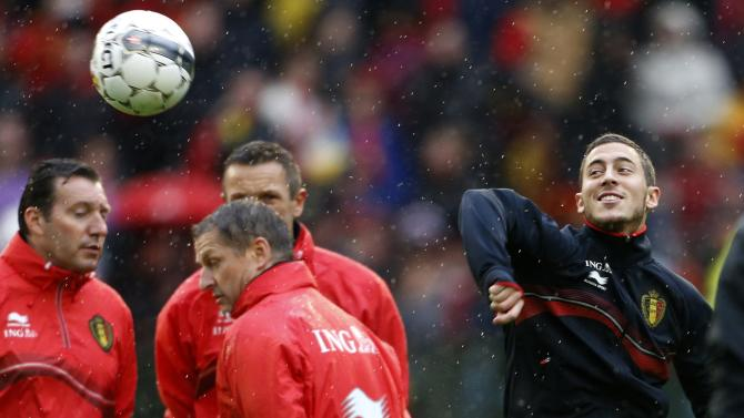 Belgium's soccer team player Hazard controls the ball past coach Wilmots during a training session in Brussels