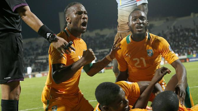 Ivory Coast's Didier Drogba, left, and Sio Giovanni, right, celebrate with their teammates after scoring a goal in a World Cup 2014 qualifying match between Ivory Coast and Senegal at Mohammed V stadium in Casablanca, Morocco, Saturday Nov. 16, 2013. Ivory Coast qualified for the World Cup tournament by beating Senegal 4-2 on aggregate in a playoff for next year's finals in Brazil after a 1-1 draw