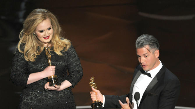 "Singer Adele, left, and musician/producer Paul Epworth accept the award for best original song for ""Skyfall"" from ""Skyfall"" during the Oscars at the Dolby Theatre on Sunday Feb. 24, 2013, in Los Angeles.  (Photo by Chris Pizzello/Invision/AP)"