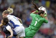 US goalkeeper Hope Solo (R) saves a ball past France's Eugenie Le Sommer (L) during their group G Olympic Women's football match at Hampden Park in Glasgow. US defeated France 4-2. A