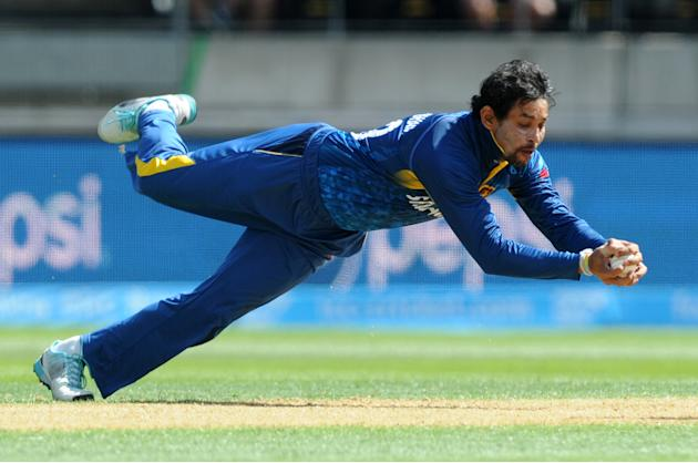 Sri Lankan bowler T.M.Dislshan takes a catch to dismiss England's Gary Balance during their Cricket World Cup match in Wellington, New Zealand, Sunday, March 1, 2015. (AP Photo Ross Setford)