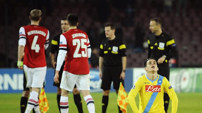 Napoli's Jose Callejon, foreground right, reacts at the end of a Champions League, group F, soccer match between Napoli and Arsenal, at the Naples San Paolo stadium, Italy, Wednesday, Dec. 11, 2013. Ten-man Arsenal advanced to the Champions League knockout phase for the 14th consecutive year despite a 2-0 loss Wednesday at Napoli, which was eliminated. Gonzalo Higuain scored in the 73rd minute but the San Paolo stadium was soon silenced when word arrived that Borussia Dortmund had scored a late goal in a 2-1 win at Marseille to win Group F