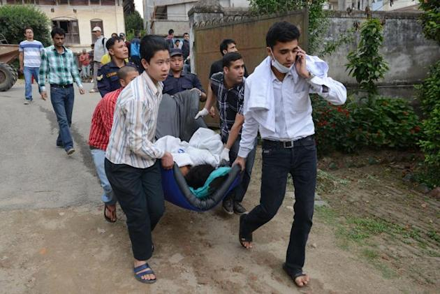 Nepalese health workers carry injured people into an open area following an 7.9 earthquake on the outskirts of Kathmandu, on April 25, 2015