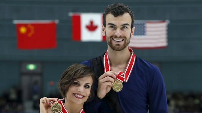Gold medal winners in the pairs competition, Meagan Duhamel and Eric Radford of Canada show off their medals during the presentation ceremony at the ISU Grand Prix of Figure Skating in Nagano, Japan