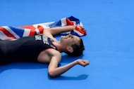 Britain's Alistair Brownlee lays exhausted with the Union flag after winning the men's triathlon event at the London 2012 Olympic Games on August 7, 2012 in London