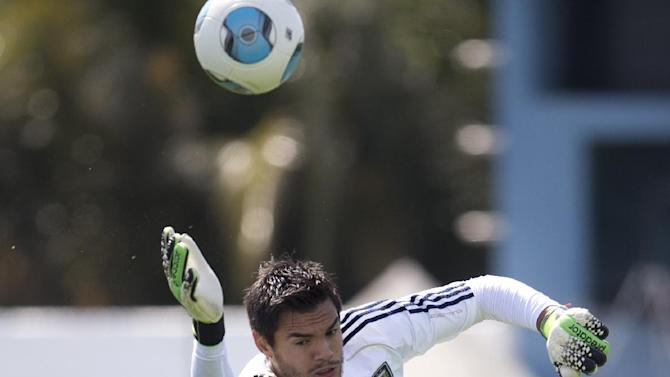 Argentina's Sergio Romero jumps to save a ball during a team training session ahead a Brazil 2014 World Cup qualifying soccer match against Peru in Buenos Aires, Argentina, Tuesday, Oct. 8, 2013