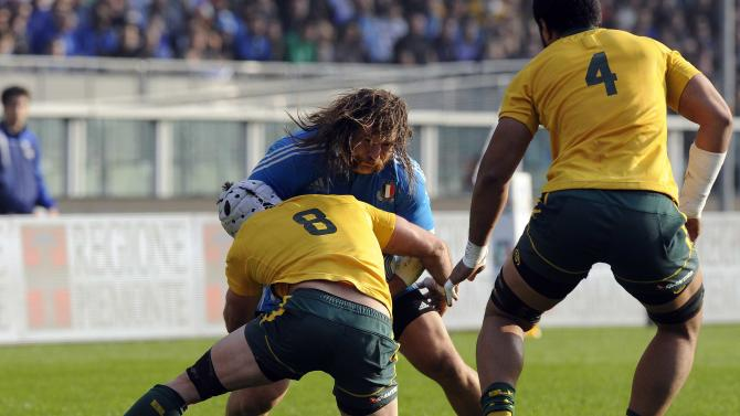 Italy's Martin Castrogiovanni is tackled by Australia's Ben Mowen and Sitaleki Timani during their Six Nations rugby union match at the Olympic stadium in Turin