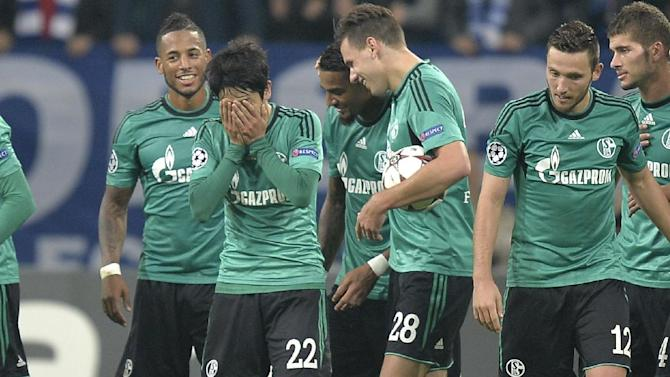 Schalke's Atsuto Uchida, second from left, covers his face as he celebrates with teammates after scoring the opening goal during the Champions League Group E soccer match between FC Schalke 04 and Steaua Bucharest  in Gelsenkirchen, Germany, Wednesday, Sept. 18, 2013