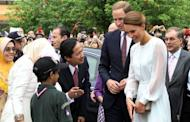 "Prince William and his wife Catherine, the Duchess of Cambridge, meet with students while walking in the gardens of the KLCC in Kuala Lumpur on September 14. The British royal family have warned an Italian magazine that ""unjustifiable upset"" would be heaped on Catherine if it went ahead and printed topless photos of her"