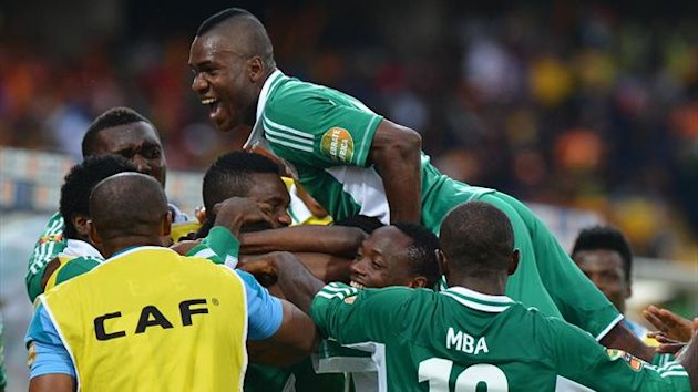 Nigeria's forward Emmanuel Emenike (hidden) is congratulated by teammates after scoring a goal during the African Cup of Nations