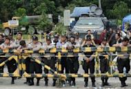 Police stand guard behind a barricade as they watch Freeport McMoRan gold and copper mine workers hold a strike in Timika in July, 2011. US mining giant Freeport McMoRan's Indonesian subsidiary has suspended its operations due to fighting among workers, its spokesman said, in the latest problem to hit the troubled mine