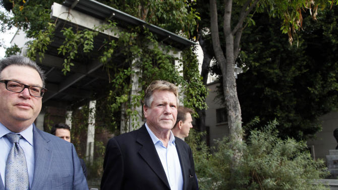 Actor Ryan O'Neal, right, leaves court after he testified in a Los Angeles courtroom on Monday, Dec. 2, 2013, about his relationship with Farrah Fawcett and his claimed ownership of an Andy Warhol portrait of the actress. The Oscar-nominated actor is being sued by the University of Texas at Austin, which is seeking to gain possession of the portrait which it claims the actress bequeathed to the university. (AP Photo/Nick Ut)