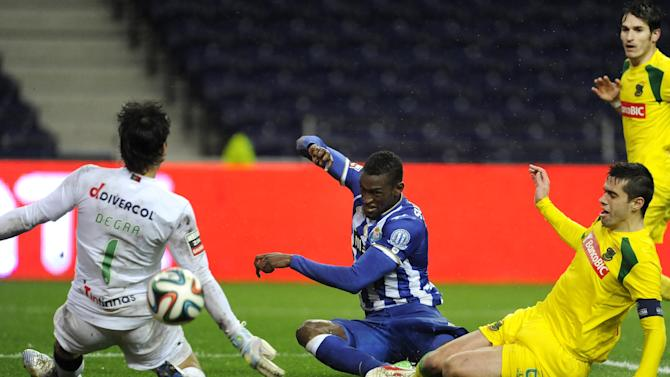 FC Porto's Jackson Martinez, from Colombia, scores his side's second goal past Pacos Ferreira's goalkeeper Matias Degra, from Italy, and Tiago Valente, right, in a Portuguese League soccer match at the Dragao stadium in Porto, Portugal, Sunday, Feb. 9, 2014. Jackson scored once in Porto's 3-0 victory