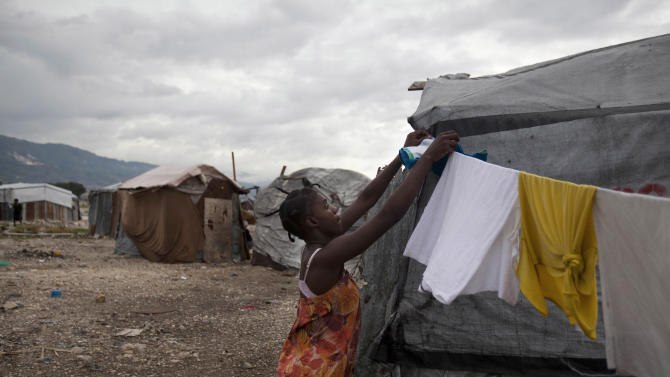 A woman fixes a clothes line next to her tent under cloudy skies caused by the nearby passing of Tropical Storm Chantal at the Jean-Marie Vincent camp for people displaced by the 2010 earthquake in Port-au-Prince, Haiti, Wednesday, July 10, 2013. Tropical Storm Chantal skirted the southern coasts of the Dominican Republic and Haiti on Wednesday, losing force but heavy rain still posed a threat to some of the region's most vulnerable people. (AP Photo/Dieu Nalio Chery)