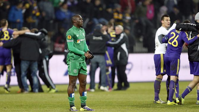 Wigan's Marc-Antoine Fortune, center, looks on as Maribor players celebrate their victory in their group D Europa League soccer match, in Maribor, Slovenia, Thursday, Dec. 12, 2013