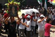 "A handout image released by the Syrian opposition's Shaam News Network shows mourners carrying the coffin of Fadwa Khaled who was allegedly killed during the unrest in Qamishli. UN-Arab envoy Kofi Annan expressed ""horror"" at the Houla massacre of more than 100 people as he began a visit on Monday to the Syrian capital aimed at salvaging his battered peace plan"