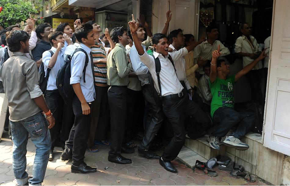 Indian fans celebrate as they watch cricketer Sachin Tendulkar scoring his 100th century, on a television set from outside a shop in Mumbai on March 16, 2012. India's Sachin Tendulkar became the f