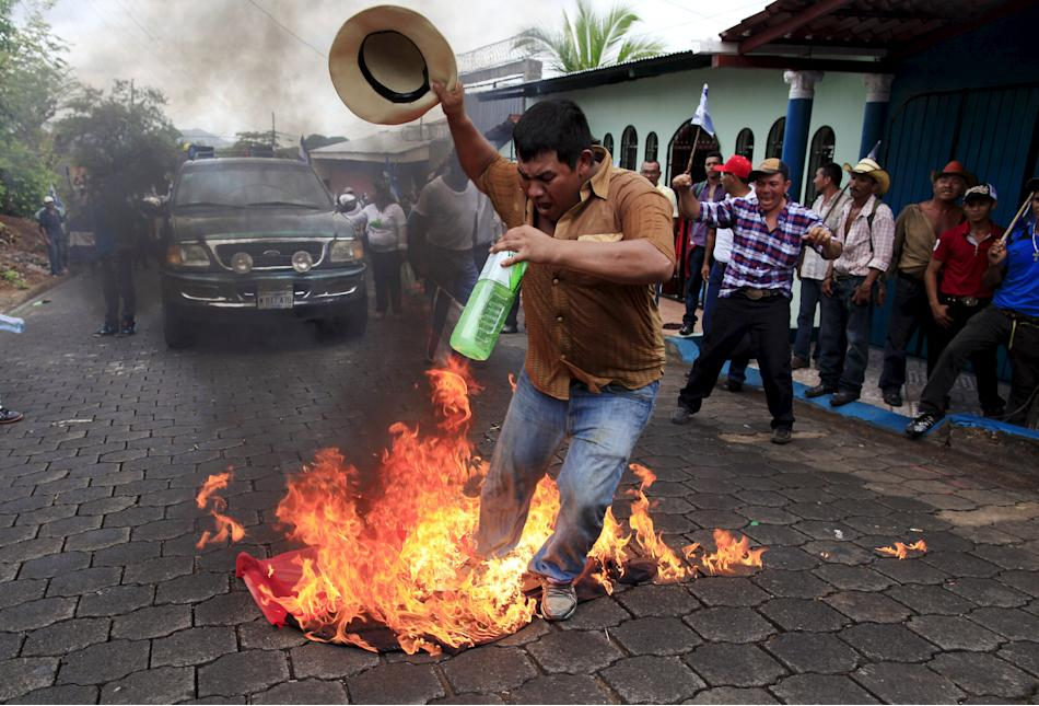 A protester burns a Sandinista flag during a march to protest against the construction of the interoceanic Grand Canal in Juigalpa City, Nicaragua