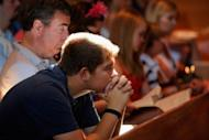 Parishioners pray during morning mass remembering victims of the theater shooting at Our Lady of Loreto Catholic Church in Aurora, Colorado. US President Barack Obama landed in Colorado on Sunday to meet relatives of those gunned down in the Aurora cinema massacre, after residents flocked to church services to remember the 12 dead