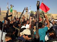Shiite tribal fighters raise their weapons and chant slogans against the al-Qaida-inspired Islamic State of Iraq and the Levant (ISIL) in the east Baghdad neighborhood of Kamaliya, Iraq, Sunday, June 15, 2014. Emboldened by a call to arms by the top Shiite cleric, Iranian-backed militias have moved quickly to the center of Iraq's political landscape, spearheading what its Shiite majority sees as a fight for survival against Sunni militants who control of large swaths of territory north of Baghdad. (AP Photo)