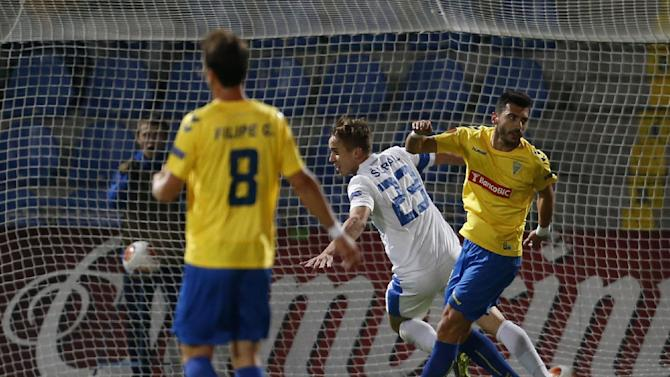 Jasef Sural, center, of Slovan Liberec runs past Filipe, left, and Bruno Miguel, right, both of Estoril Praia to celebrate after scoring during their Europa League Group H soccer match in Liberec, Czech Republic, Thursday, Oct. 3, 2013