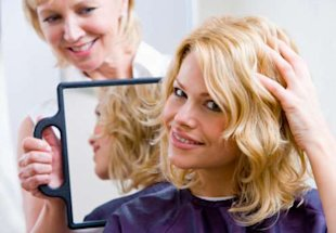 hairdresser holding up mirror for woman with new haircut