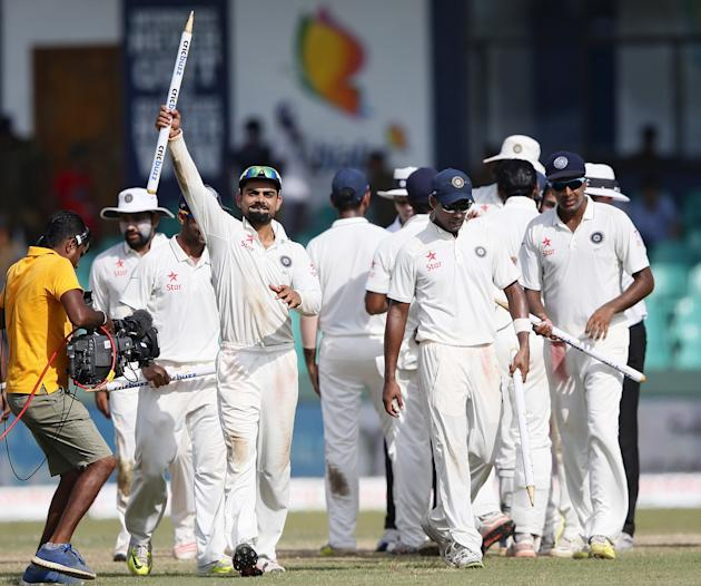 India's captain Kohli shows a stump as he celebrates with his teammates Binny and Ashwin after they won their final test cricket match and the series against Sri Lanka in Colombo