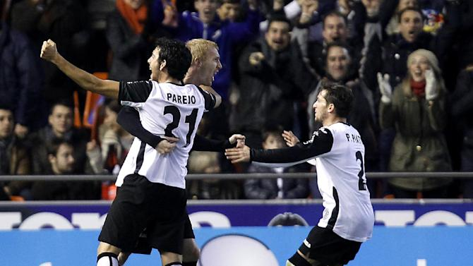 Valencia's Jeremy Mathieu from France, center, celebrates after scoring against Real Madrid  during their La Liga soccer match at the Mestalla stadium in Valencia, Spain, Sunday, Dec. 22, 2013