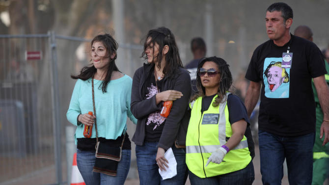 A injured woman, second left, holds her arm as she walks with medical personnel, second right, after she and others were injured during a concert by Linkin Park in Cape Town, South Africa, Saturday, Nov. 7, 2012. The city of Cape Town, South Africa, says that 20 people have been injured after scaffolding collapsed because of high winds outside a concert for Linkin Park. (AP Photo)