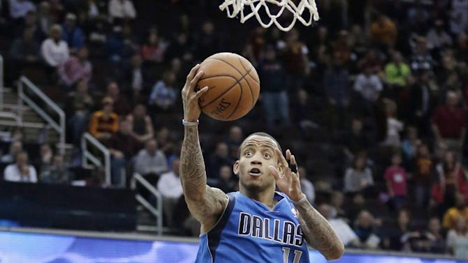 Dallas Mavericks' Monta Ellis (11) jumps to the basket against Cleveland Cavaliers' Kyrie Irving (2) during the fourth quarter of an NBA basketball game Monday, Jan. 20, 2014, in Cleveland. Irving was called for the foul. Ellis scored a team-high 22 points for the Mavericks 102-97 win