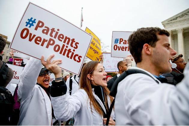 FILE - In this March 4, 2015 file photo, demonstrators rally outside the Supreme Court in Washington, as the court was hearing arguments in President Barack Obama's health overhaul which, if succe