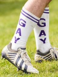 "Berlin Bruisers captain Colin Comfort wears socks reading ""Gay"" on them during a training with Welsh rugby player Gareth Thomas on May 23, 2014 in Berlin"