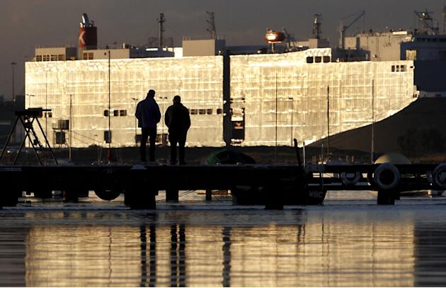 File photo of people silhouetted against the hulk of a car carrier ship docked in Melbourne