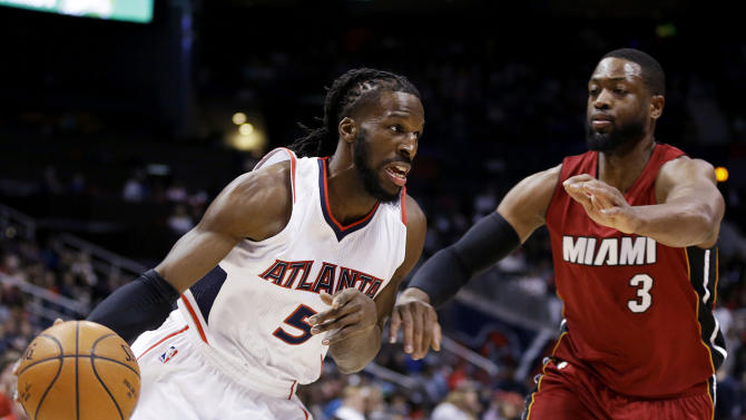 Atlanta Hawks' DeMarre Carroll, left, dribbles against Miami Heat's Dwyane Wade during the first quarter of an NBA basketball game Friday, March 27, 2015, in Atlanta. (AP Photo/David Goldman)