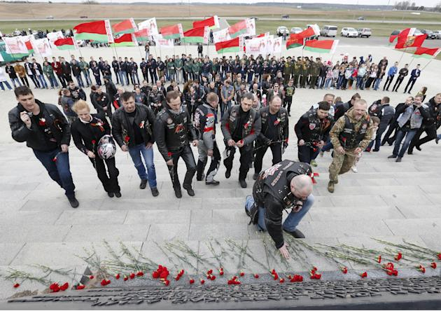 Participants of bike ride commemorating 70th anniversary of victory over Nazi Germany in World War Two lay flowers at war memorial Mound of Glory outside Minsk