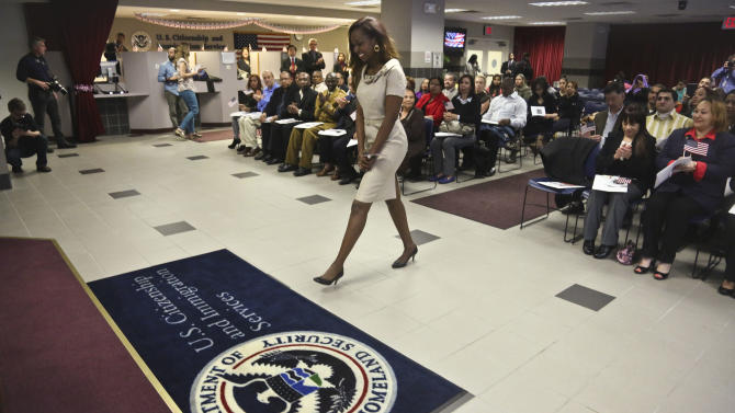 "Immaculee Ilibagiza walks to the podium to address fellow immigrants from 16 different countries, during the U.S. Citizenship and Immigration Services  naturalization ceremony on Wednesday, April 17, 2013 in New York.  Ilibagiza, author of the best seller ""Left to Tell, Discovering God Amidst the Rwandan Holocaust,"" told her story of hiding in a 3-by-4 foot bathroom with seven other women and girls before fleeing the 1994 Rwandan genocide, which claimed more than 500,000 lives.  (AP Photo/Bebeto Matthews)"