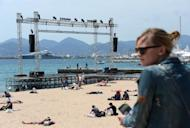 People sit on the beach next to a podium where films will be projected on a giant screen on the eve of the 65th Cannes film festival