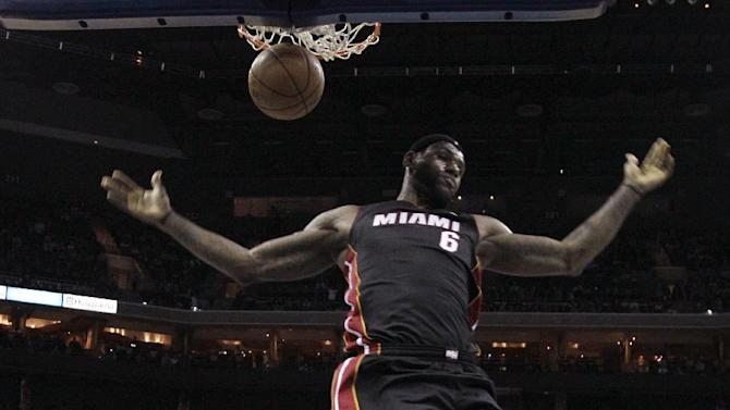 Miami Heat's LeBron James (6) reacts after dunking against the Charlotte Bobcats during the first half of an NBA basketball game in Charlotte, N.C., Saturday, Nov. 16, 2013