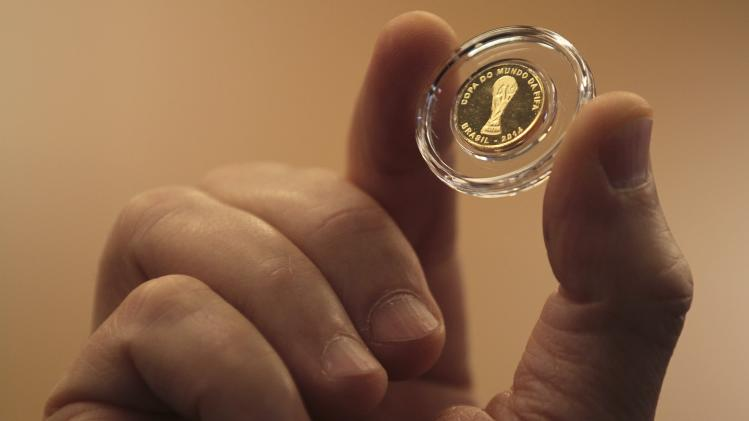 Worker from Brazil's Central Bank holds a FIFA 2014 World Cup commemorative gold coin during its launch ceremony in Brasilia