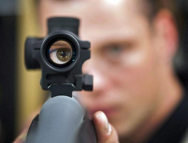 "Patrick Deegan looks through the scope of a rifle in Calgary, Sept. 15, 2010.A man who a judge says has an ""obsession with warfare and weaponry"" has been sent to jail for threatening to kill"