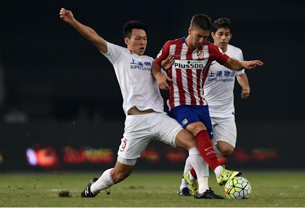 Atletico Madrid's Argentina forward Luciano Vietto (centre) is challenged by Shanghai's midfielder Jiajie Wang (left) and Argentinian forward Dario Conca during a friendly match in Shanghai on