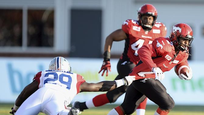 Montreal Alouettes' Volny grabs the jersey of Calgary Stampeders' Brown during the second half of their CFL football game in Calgary